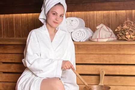 Beautiful young woman in a white towel is relaxing in a sauna. Sauna made of wood. Concept: relaxation, wellness center
