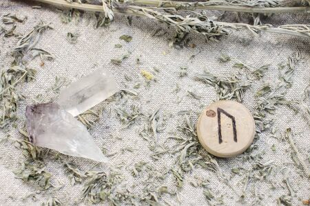 Scandinavian wooden rune Uruz on a rough linen cloth with amethyst crystalline, rock crystal and dried wormwood. Standard-Bild