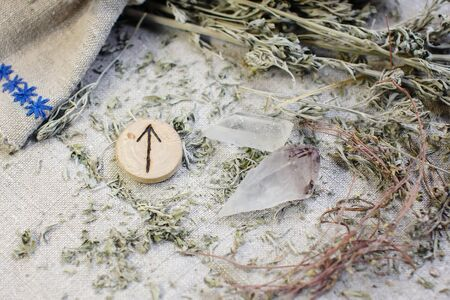 Scandinavian wooden rune Tiwaz, Teiwaz , Tir on a rough linen cloth with amethyst crystalline, rock crystal and dried wormwood.