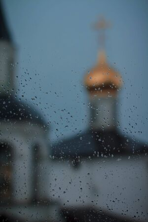 orthodox church behind glass with raindrops, Moscow
