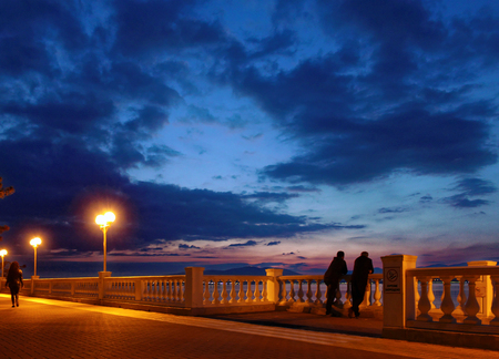 Seafront at night bright lights blue sky