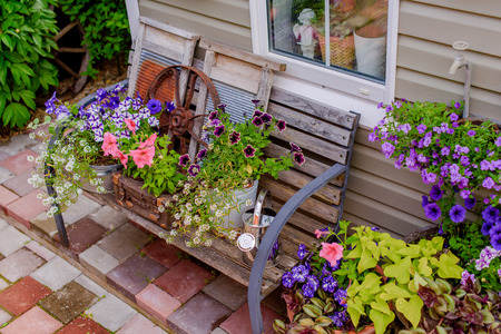ideally: Beautifully decorated porch of a private house, colorful flowers in large clay pots, vintage bench, vintage inventory.