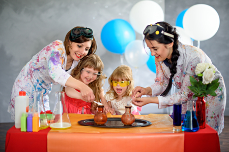 Two crazy professor carried out chemical experiments in the laboratory. Birthday little girl.