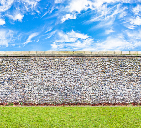 stone wall with the green lawn and skies horizontal seamless image photo