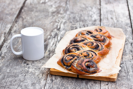 half stuff: Poppy seed roll freshly baked on the table with white mug of the milk Stock Photo
