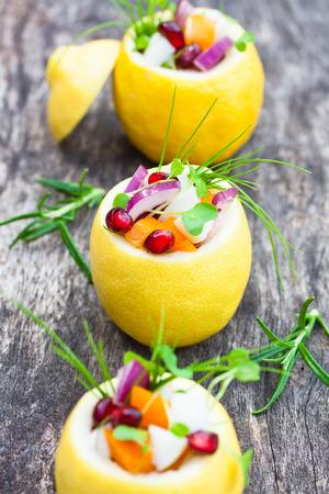 amuse: stuffed lemons with vegetarian salad on the old table