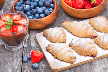 fresh croissants and berries with cup of fruit tea on old wooden table photo