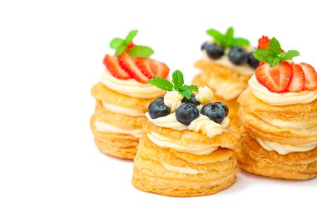 domowe ciasto francuskie nadziewane kremem i jagody na białym