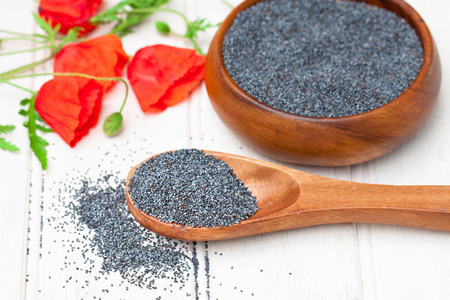 poppy seeds: poppy  seeds in a wooden bowl on a table with spoon
