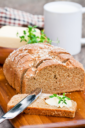 bread soda: Sliced  Irish stoneground soda bread with butter and thyme on the wooden table Stock Photo