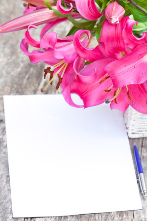 Pink  lily Robina flowers bouquet and blank paper sheet with pen on rustic wooden table