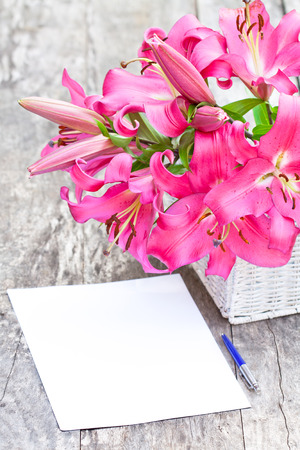 Pink  lily flowers bouquet and blank paper sheet with pen on rustic wooden table Stock Photo
