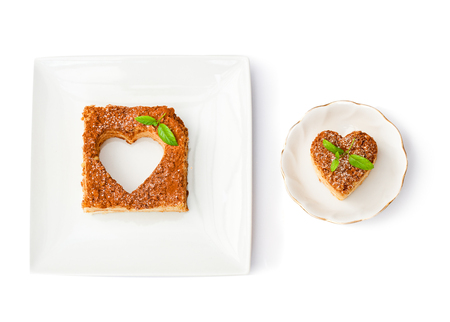 Heart shaped napoleon cake with mint on white plates isolated Stock Photo