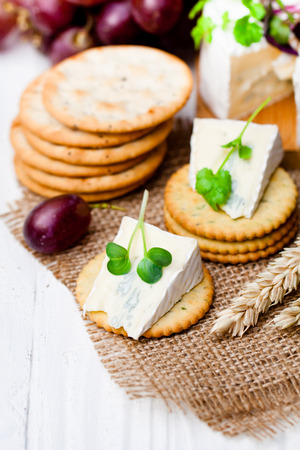 cheeseboard: Crackers  and wedge of blue camembert cheese on sackcloth napkin