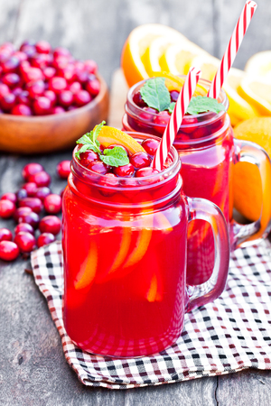 red straw: Glass  jars ofhomemade juice with orange slices and wild cranberry