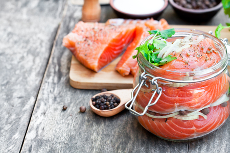 Salted  salmon in glass jar on an old wooden table