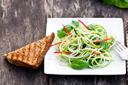 paprica: zucchini  spaghetti salad with basil and paprica on squared plate