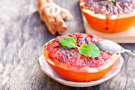 baked  grapefruit with brown sugar and cinnamon on a saucer Stock Photo
