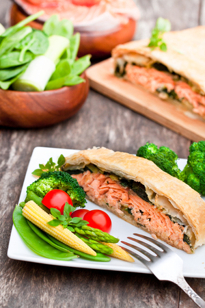 dinner jacket: Salmon  fillet on leek and spinachbaked in puff pastry with vegetables Stock Photo