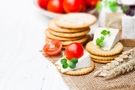 Crackers  andwedge of blue camembert cheese on sackcloth napkin Stock Photo
