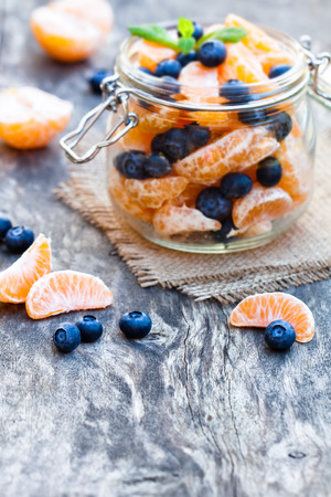 hulled: peeled tangerine or mandarin fruit and blueberry in glass jar on wooden table