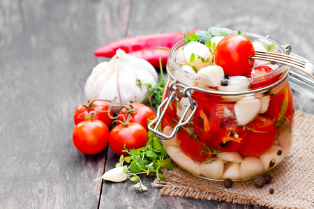 Marinated  cherry tomato with garlic and mixed chillies and herbs in glass jar
