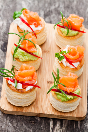 salted  puff pastry stuffed with cream cheese and smoked salmon on rustic wooden background Stock Photo