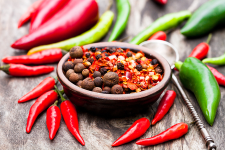 small plate: Red  hot chili peppers and other spices in a small plate on wooden background