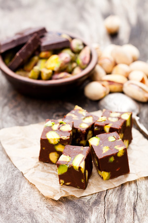 fancy sweet box: Dark  chocolate cubes with pistachios on wooden background