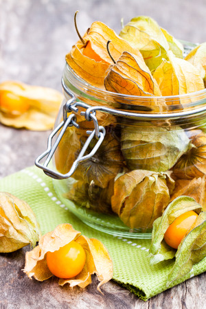 Ripe  physalis in a glass jar on wooden table Stock Photo