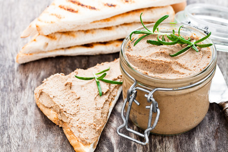 homemadeliver  pate with rosemary in a jar on a rustic wooden table Stock Photo
