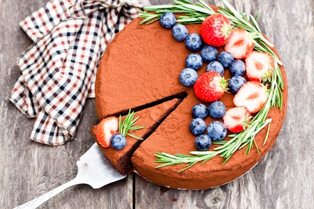 Chocolate  cheesecake with berries on wooden background