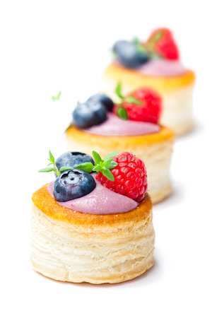 puff  pastry stuffed with soft blueberry curd with berries and thyme on white background