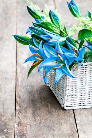 White  basket with blue lily flowers bouquet on rustic wooden table