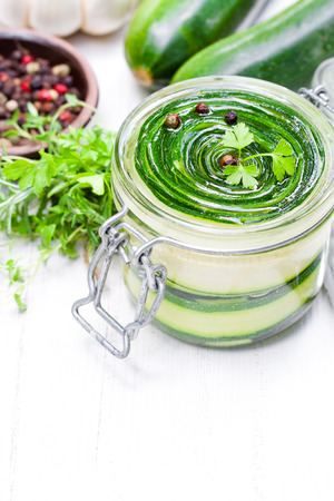 Sliced  zucchini with parsley and garlic preserves in glass jar Stock Photo