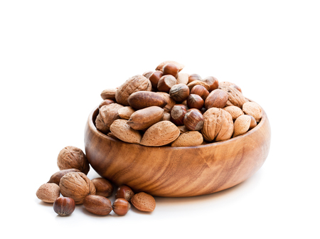 Various  nuts in wooden bowl isolated on white  Stock Photo