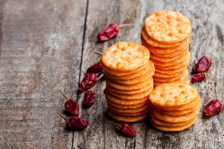 Round  shape rice cracker with chili pepper on wooden table  Stock Photo