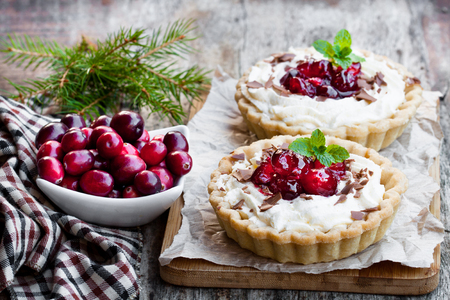 Delicious  tarts with cream and fresh cranberry on wooden table. Christmas dessert.