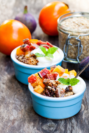 fruit  crumble with oat flakes and persimmon and fig on rustic wooden table  Stock Photo