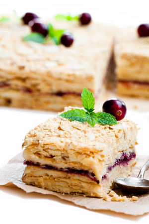 Napoleon  cake with cranberry and mint on white background