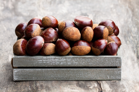 fresh  raw chestnuts in a wooden box on wooden background
