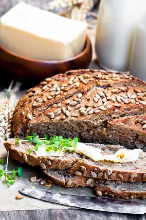 Sliced  homemade rye bread on baking paper and bottles of milk on wooden table