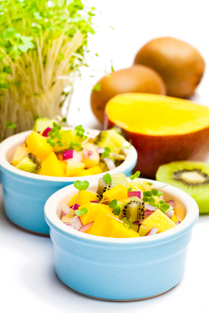 Dietetic  salad in the pot with kiwi and mango isolated on white