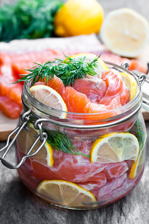 Salted  salmon with lemon in glass jar on wooden background