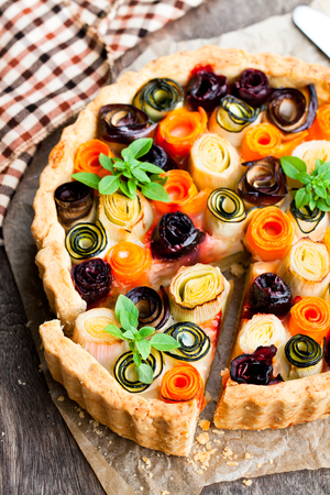 Homemade  vegetarian pie with colored rolled vegetables