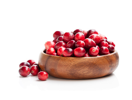 Fresh cranberries in wooden bowl isolated on white background