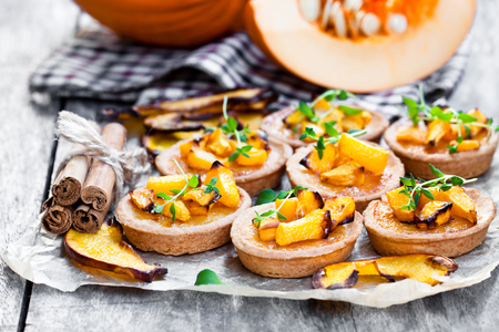 delicious  tartlets with baked honey pumpkin and cinnamon on rustic background
