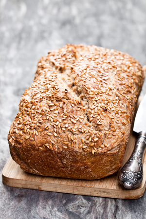 Homemade  wholemeal rye bread with flax seeds on wooden table
