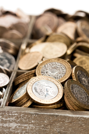 wooden  cashbox full of pound sterling coins  Stock Photo