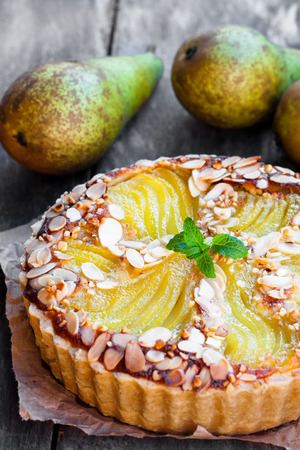 Delicious  cake with half poached pears and almond flakes